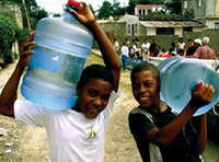 Two young boys carrying jugs of water
